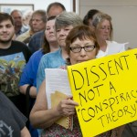 A woman who did not want her name published holds a sign at a public hearing about the Jade Helm 15 military training exercise at the Bastrop County Commissioners Court in Bastrop on Monday April 27, 2015.  An overflow crowd came to the meeting to hear a presentation and ask questions of  Lt. Col. Mark Lasatoria, of the U.S. Army Special Operations Command, about the controversial military exercise that will take place in several states this summer.   JAY JANNER / AMERICAN-STATESMAN