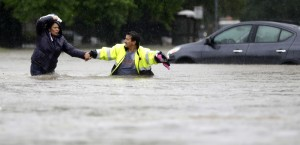 Alberto Lopez, right, helps his wife Glenda wade through floodwaters as they evacuate their flooded apartment complex Monday, April 18, 2016, in Houston. Storms have dumped more than a foot of rain in the Houston area, flooding dozens of neighborhoods and forcing the closure of city offices and the suspension of public transit. (AP Photo/David J. Phillip) ORG XMIT: TXDP117